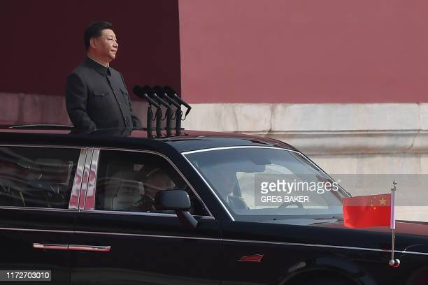 Chinese President Xi Jinping emerges from Tiananmen Gate before reviewing troops from a car during a military parade at Tiananmen Square in Beijing...