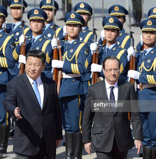 Chinese President Xi Jinping escorts French President Francois Hollande after they review an honour guard outside the Great Hall of the People in...