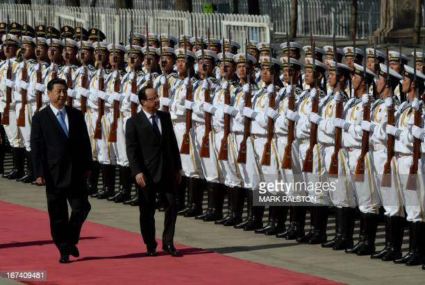 Chinese President Xi Jinping escorts French President Francois Hollande as they review an honour guard outside the Great Hall of the People in...