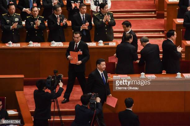 Chinese President Xi Jinping followed by Chinese Premier Li Keqiang walk to cast their ballots during the sixth plenary session of the National...