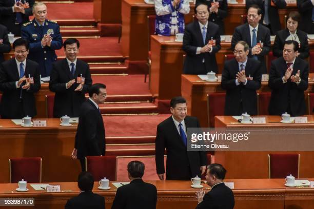 Chinese President Xi Jinping followed by Chinese Premier Li Keqiang arrive to attend the seventh plenary session of the 13th National People's...