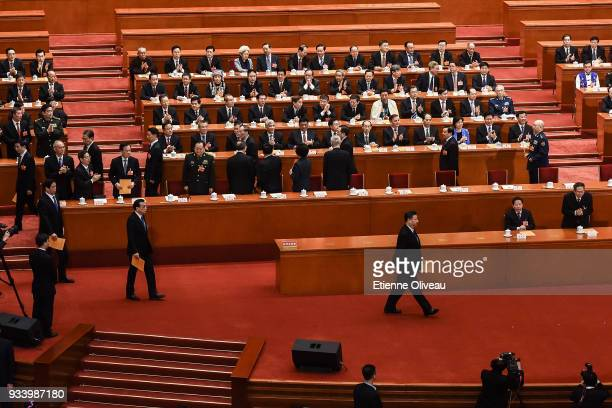 Chinese President Xi Jinping followed by Chinese Premier Li Keqiang walk to casts their votes during the seventh plenary session of the 13th National...