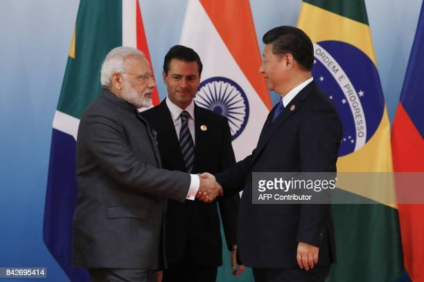 Chinese President Xi Jinping greets Indian Prime Minister Narendra Modi and Mexico's President Enrique Pena Nieto before a group photo session at the...