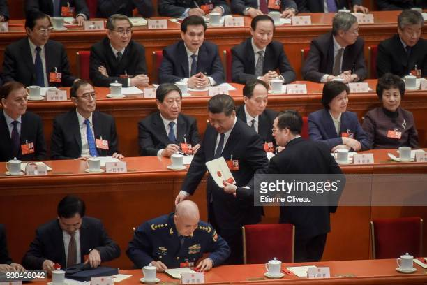 Chinese President Xi Jinping hands over a folder as he leaves during the third plenary session of the first session of the 13th National People's...