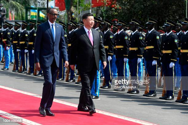 Chinese President Xi Jinping inspects a guard of honour accompanied by Rwandan President Paul Kagame upon his arrival at the Urugwiru State house in...