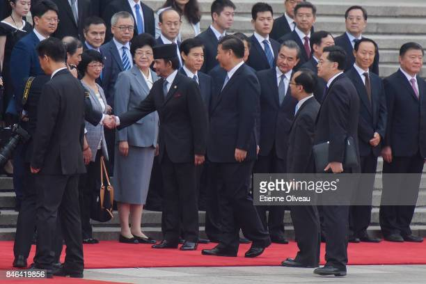 Chinese President Xi Jinping introduces the Chinese delegation to Sultan of Brunei Hassanal Bolkiah during a welcoming ceremony outside the Great...