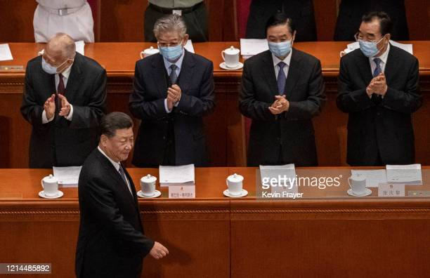 Chinese president Xi Jinping is applauded by delegates wearing protective masks as he arrives during the opening of the National People's Congress at...