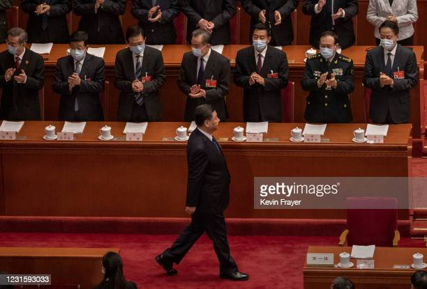Chinese President Xi Jinping is applauded by members of the government as he arrives at the second plenary session of the National People's Congress...