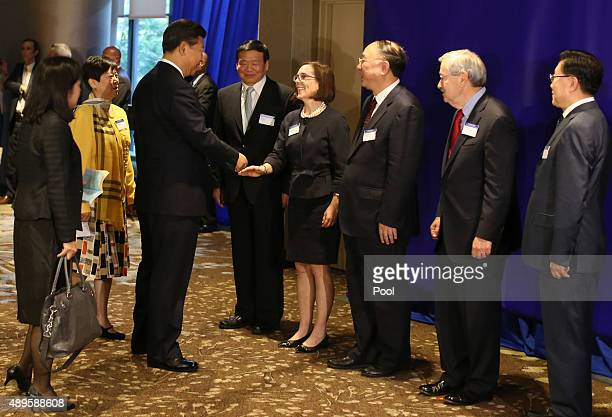 Chinese President Xi Jinping is greeted by Oregon state Gov Kate Brown at a meeting of US and Chinese governors to discuss clean technology and...