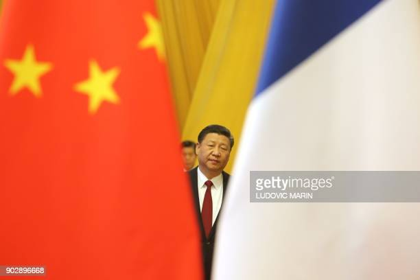 Chinese President Xi Jinping is seen between China and France's national flags in Beijing on January 9 2018 Chinese President Xi Jinping and French...