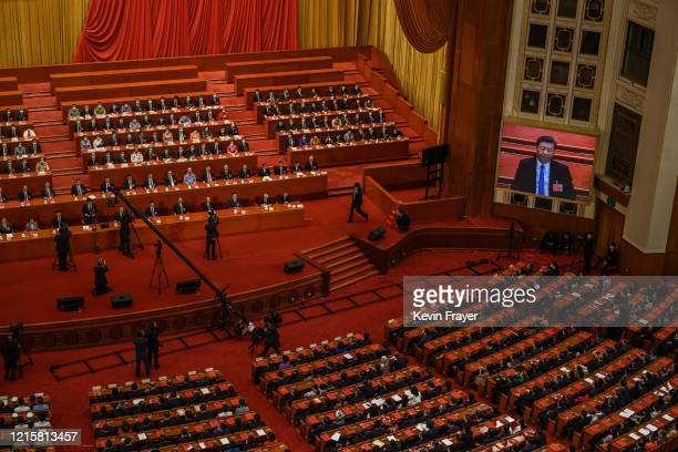Chinese president Xi Jinping is seen on a large screen as Communist Party delegates take part in a session after voting on a new draft security bill...