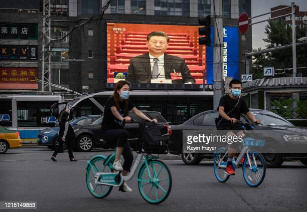 Chinese president Xi Jinping is seen on a large screen showing the evening news during a session of the National People's Congress at the Great Hall...