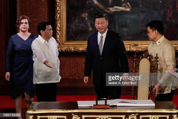 Chinese President Xi Jinping is welcomed by Philippines' President Rodrigo Duterte during a guest book signing at the Malacanang Presidential Palace...