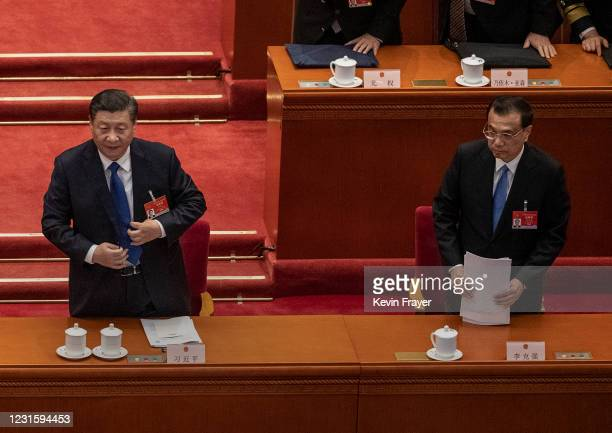 Chinese President Xi Jinping, left, and Premier Li Keqiang, right, stand to leave at the end of the second plenary session of the National People's...