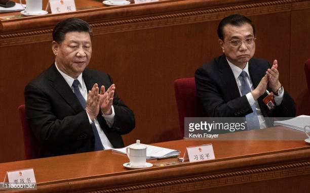 Chinese President Xi Jinping left and Prime Minister Li Keqiang applaud during the third plenary session of the National People's Congress at The...
