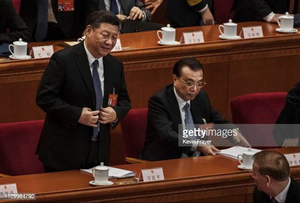 Chinese President Xi Jinping left buttons his jacket as he stands to leave next to Prime Minister Li Keqiang right at the end of the third plenary...