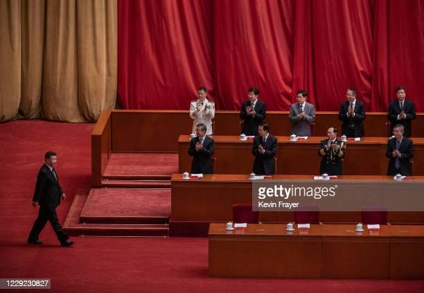Chinese President Xi Jinping, left, is applauded by senior members of the government as he arrives to speak at a ceremony marking the 70th...