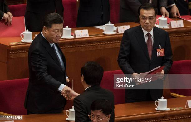 Chinese President Xi Jinping left shakes hands with a government official as Prime Minister Li Keqiang looks on during the closing meeting of the...