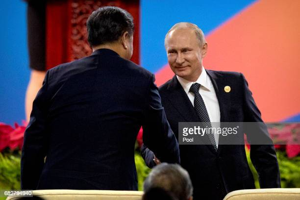 Chinese President Xi Jinping left shakes hands with Russian President Vladimir Putin after Putin spoke during the opening ceremony of the Belt and...
