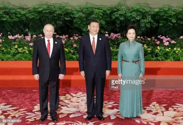 Chinese President Xi Jinping poses next to his wife Peng Liyuan and Russian President Vladimir Putin at the welcoming banquet for the Belt and Road...
