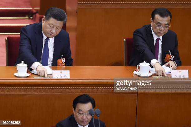 Chinese President Xi Jinping , Premier Li Keqiang and member of the Central Political Bureau Li Zhanshu vote during the third plenary session of the...