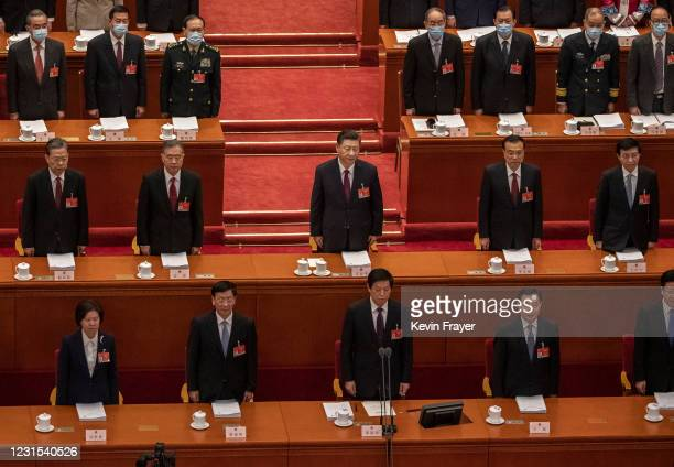 Chinese President Xi Jinping , Premier Li Keqiang and members of the government stand during the national anthem at the opening session of the...