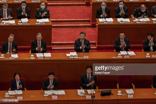 Chinese President Xi Jinping , Premier Li Keqiang and members of the government applaud during the national anthem at the opening session of the...