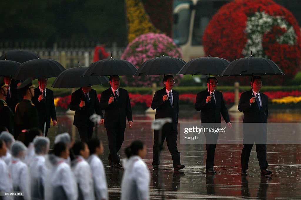 Chinese President Xi Jinping (Right), Premier Li Keqiang, members of the Politburo Standing Committee Zhang Dejiang, Yu Zhengsheng, Liu Yunshan, Wang Qishan and Zhang Gaoli hold umbrellas as they arrive for a tribute ceremony marking the 64th anniversary of the founding of the People's Republic of China at Tiananmen Square on October 1, 2013 in Beijing, China. On October 1, 1949, Chinese leader Mao Zedong stood at the Tiananmen Rostrum to declare the founding of the People's Republic of China.