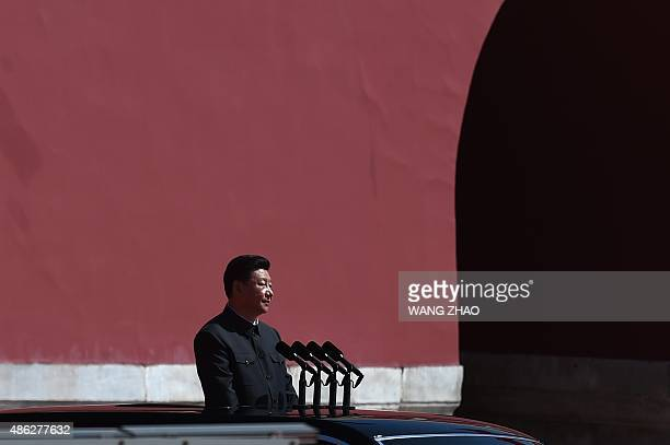 Chinese President Xi Jinping prepares to review People's Liberation Army troops from a car during a military parade in Tiananmen Square in Beijing on...
