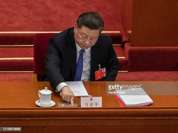 Chinese president Xi Jinping presses the green button as he votes on a new draft security bill for Hong Kong during the closing session of the...
