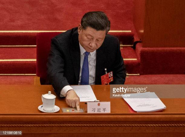 Chinese President Xi Jinping presses the green button as he votes during the closing session of the National People's Congress at the Great Hall of...
