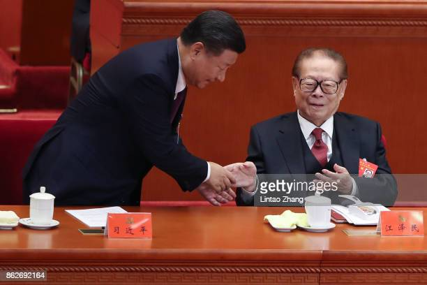 Chinese President Xi Jinping shake hands China's former president Jiang Zemin at the opening session of the Chinese Communist Party's Congress at the...