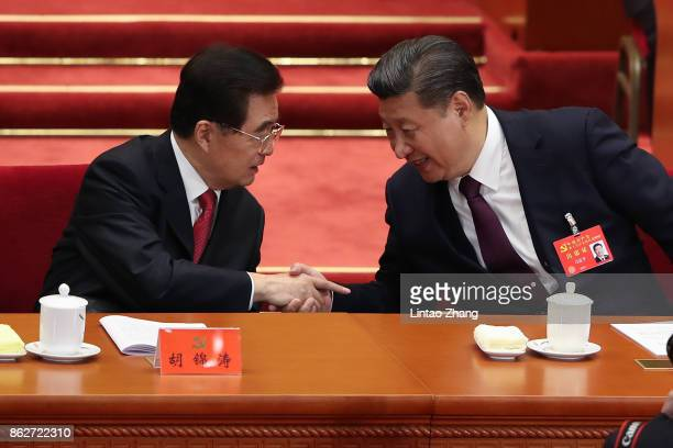 Chinese President Xi Jinping shake hands with Hu Jintao China's former president during the opening session of the Chinese Communist Party's Congress...