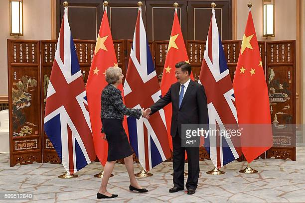 Chinese President Xi Jinping shakes hand with British Prime Minister Theresa May before their meeting at the West Lake State House in Hangzhou on...