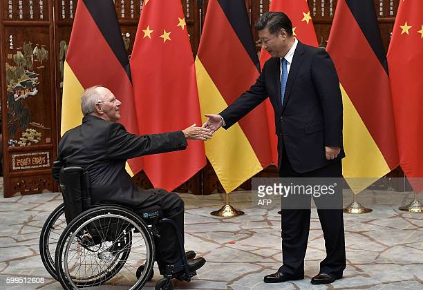 Chinese President Xi Jinping shakes hand with Chinese President Xi Jinping shakes hand with German Finance Minister Wolfgang Schauble before their...