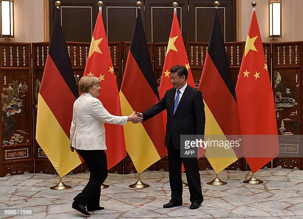 Chinese President Xi Jinping shakes hand with German Chancellor Angela Merkel before their meeting at the West Lake State House in Hangzhou on...