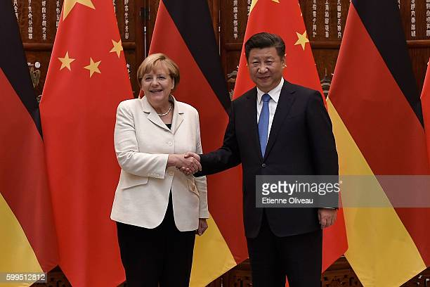 Chinese President Xi Jinping shakes hand with German Chancellor Angela Merkel before their meeting at the West Lake State House on September 5, 2016...