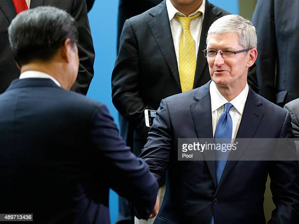 Chinese President Xi Jinping shakes hands with Apple CEO Tim Cook during a gathering of CEOs and other executives at the main campus of Microsoft...