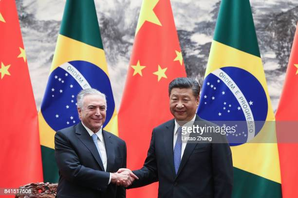 Chinese President Xi Jinping shakes hands with Brazilian President Michel Temer during the signing ceremony at the Great Hall of the People on...