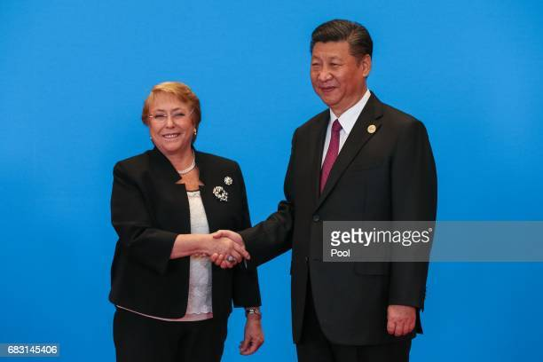 Chinese President Xi Jinping shakes hands with Chilean President Michelle Bachelet as they attend the welcome ceremony at Yanqi Lake during the Belt...