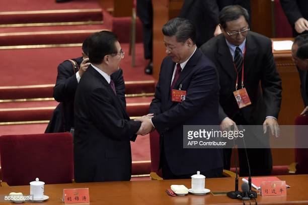 Chinese President Xi Jinping shakes hands with China's former president Hu Jintao during the closing of the 19th Communist Party Congress at the...