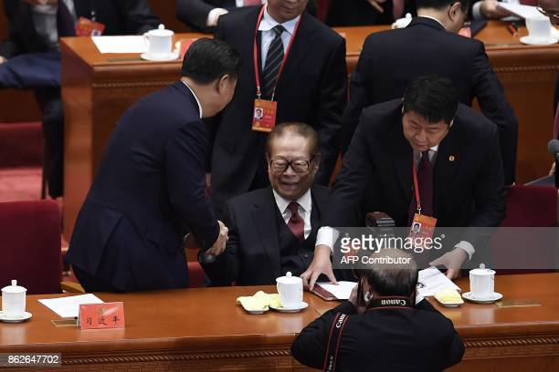Chinese President Xi Jinping shakes hands with China's former president Jiang Zemin at the opening session of the Chinese Communist Party's Congress...