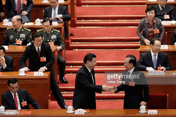 Chinese President Xi Jinping shakes hands with former Chinese Premier Wen Jiabao during the fifth plenary meeting of the National People's Congress...