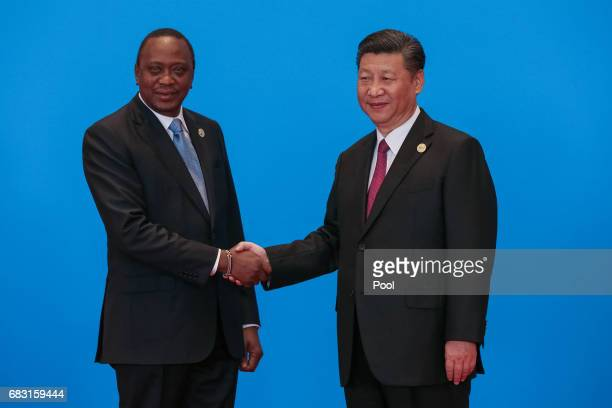 Chinese President Xi Jinping shakes hands with Kenyan President Uhuru Kenyatta as they attend the welcome ceremony at Yanqi Lake during the Belt and...
