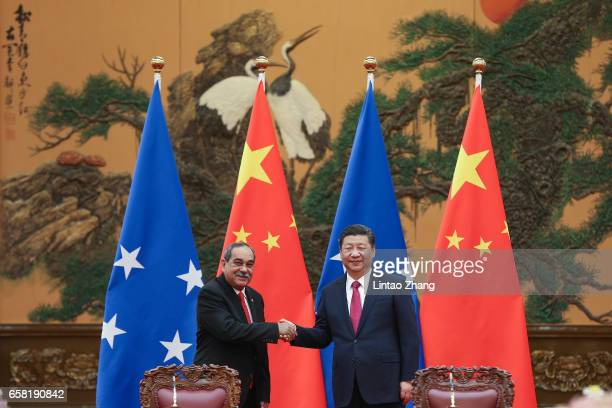 Chinese President Xi Jinping shakes hands with Micronesia's President Peter Christian during a signing ceremony at the Great Hall of the People on...