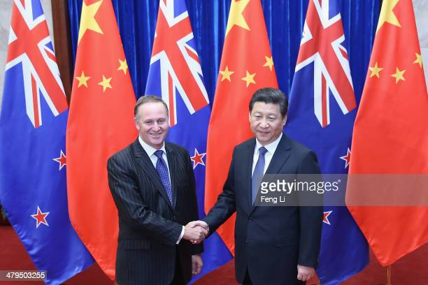 Chinese President Xi Jinping shakes hands with New Zealand Prime Minister John Key at the Great Hall of the People on March 19 2014 in Beijing China...