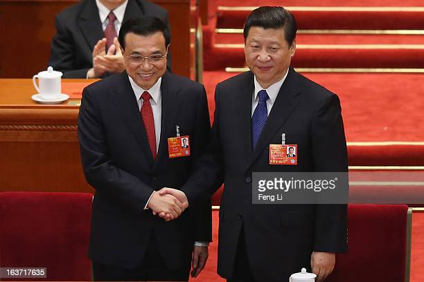 Chinese President Xi Jinping shakes hands with newlyelected Premier Li Keqiang as former Chinese Premier Wen Jiabao looks on during the fifth plenary...