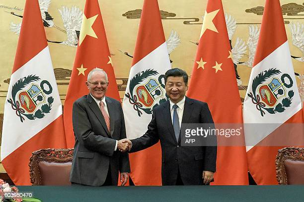 Chinese President Xi Jinping shakes hands with Peruvian President Pedro Pablo Kuczynski after a signing ceremony at the Great Hall of the People in...