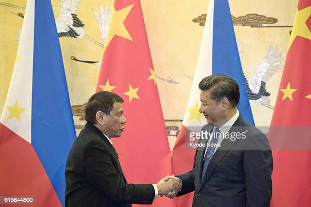 Chinese President Xi Jinping shakes hands with Philippine President Rodrigo Duterte during a signing ceremony at the Great Hall of the People in...