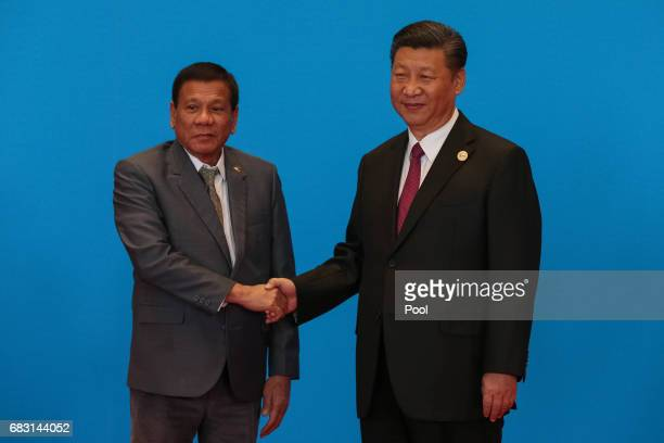 Chinese President Xi Jinping shakes hands with Philippines President Rodrigo Duterte as they attend the welcome ceremony at Yanqi Lake during the...